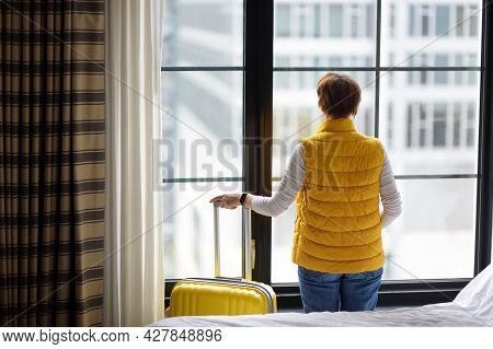 Woman Tourist Stays In Hotel Room In New York. Traveler With Suitcase Looks And Admires Of Amazing V
