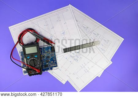 Printed Drawings Of Electrical Circuits, An Electronic Circuit Board And A Multimeter On A Purple Ba