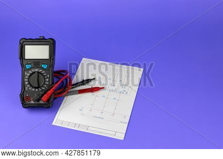 Printed Drawings Of Electrical Circuits And Digital Multimeter On A Purple Background. Repair And Di