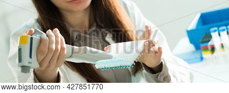 student woman with multi pipette and other PCR items in microbiological   genetic laboratory