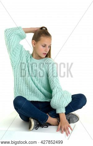 Teenage Girl Sitting On Floor With Crossed Legs. Girl With Ponytail Wearing Fashionable Outfit Sitti