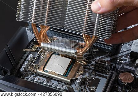 A Technician Installs An Aluminum Air-cooled Heatsink On A Desktop Pc Cpu. Air Cooler Cpu. Pc Assemb
