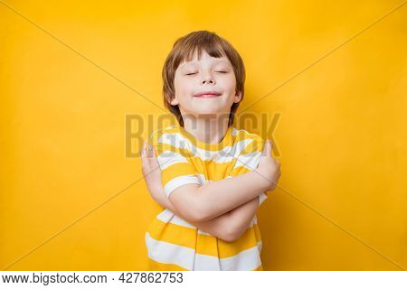 Cute Kid Boy Smiling With Pleasure While Embracing Himself, Keeping Arms Around His Shoulders. Body