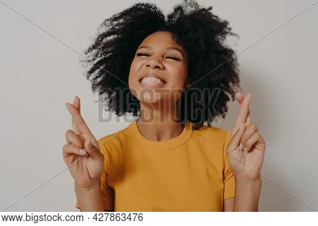 Head Shot Smiling Beautiful African American Girl With Closed Eyes Crossing Fingers Wishing Good Luc