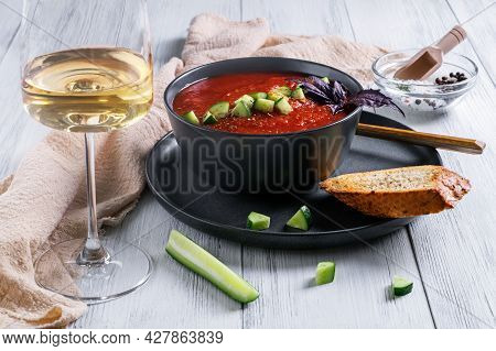 A Close-up Of A Bowl Of Spanish Traditional Cold Tomato And Cucumber Gazpacho Soup And A Glass Of Wh