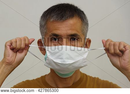 A Senior Adult Asian Man Weraing Cloth Mask On Medical Face Mask. Double Face Mask Highly Protect Co