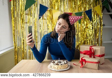 Young Woman Sits At A Birthday Table With A Sad Expression On Her Face, A Festive Cap Is Dressed On