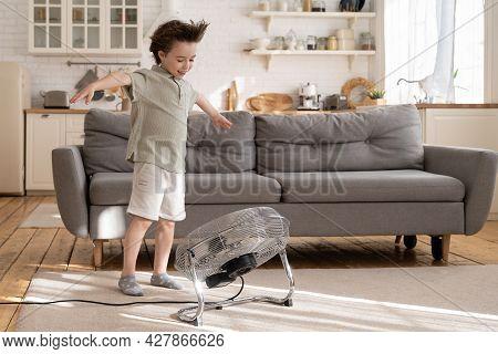 Little Preschool Boy Enjoy Fresh Air Flow From Fan. Cute Small Kid Play With Ventilator Blowing Cool