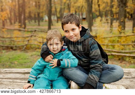 Two Brothers Play Outdoors In Autumn, Best Friends. Two Happy Boys In The Woods. Cute Brothers Who A