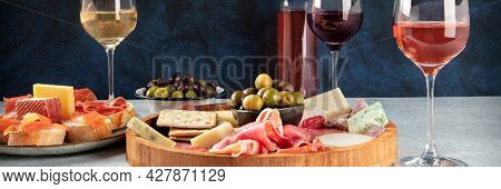 Italian Antipasti Or Spanish Tapas Panorama With Wine, Cold Meat And Cheese. Rose, White And Red Win
