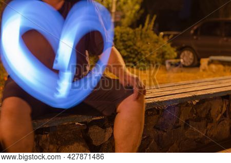 Defocused Shot Of Adult Man Gesturing With Blue Light On City Bench At Night. Male Hand Draws Heart