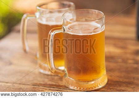 Two Beer Mugs Closeup On Wooden Natural Table.two Glass Beer On Wood Background.natural Light.
