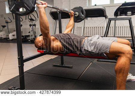 Bench Press Exercise.athletic Man Pumping Up Muscles On Bench Press At The Gym.breast Muscles Pumpin