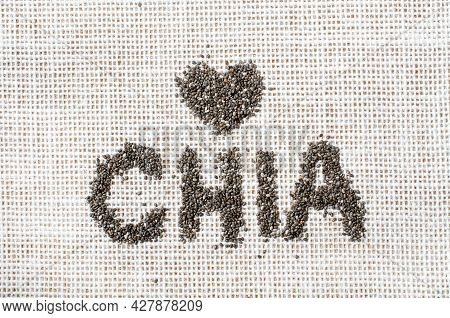Dry Organic Chia Seed In A Word Chia With Little Heart Shape On White Sack Fabric Texture Background