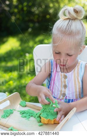 Little Cute Girl With Blonde Hair Playing With Kinetic Sand Outdoors In The Backyard In Summer Day