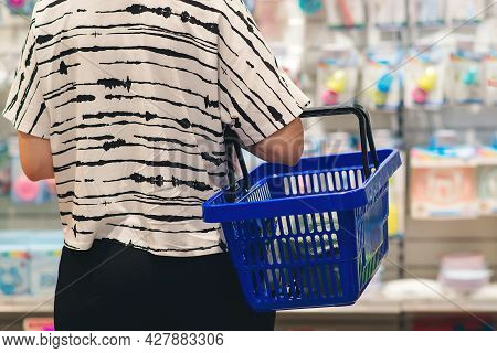 Pregnant Woman Shopping In Baby Store. Woman Choosing Baby Stuff At Baby Shop Store. Mom Is Choosing