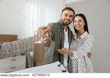 Real Estate Agent Giving Key To Happy Young Couple In New House