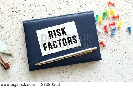 Text Risk Factors On A Business Card Lying On A Blue Notebook Next To The Glasses.