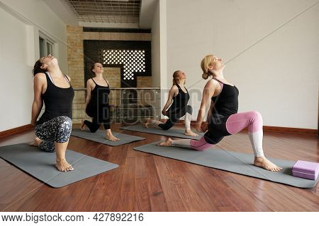 Women Attending Indoor Yoga Class And Doing Low Crescent Lunge Pose That Engaging Many Muscles