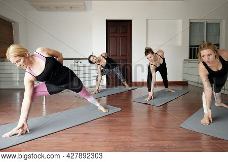 Group Of Fit Young Women Attending Yoga Class And Doing Low Lunge Pose With Forward Bend