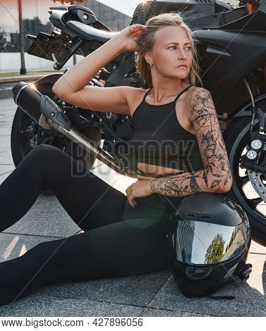 Mid Adult Woman With Tattoo And Motorcycle On City Street