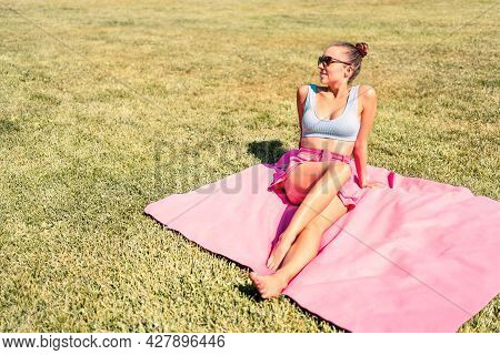 Stylish Trendy Woman Sunbathing On Picnic Blanket And Green Grass. Fit Model With Pretty Legs Lying