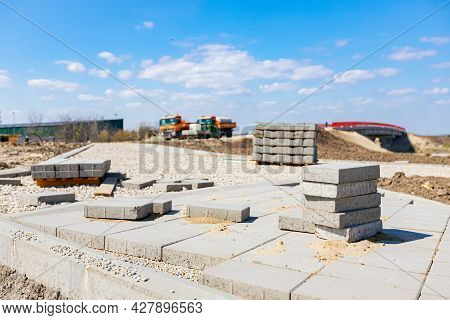 Bricklayer Placed Grey Concrete Paving Stone Blocks For Building Sidewalk Path.