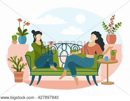 Women Sitting On Decorative Sofa In Interior Indoor Plants. Two Girls Drinking Tea And Talking In Re