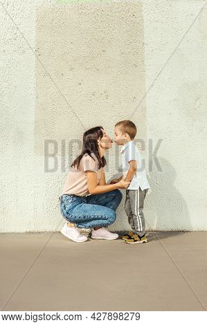 Mother And Little Son Kiss Near Wall.