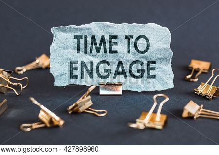 A Scrap Of Blue Paper With Clips On A Gray Background With The Text - Time To Engage.