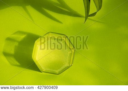 Glass Of Fresh Cold Water On A Bright Green Background Among Green Foliage With Contrasting Shadows