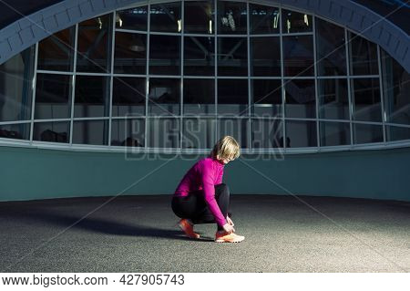 Active Female Runner Tighten Up Her Shoelaces During Jogging Training Exercise Outdoor. Horizontal S