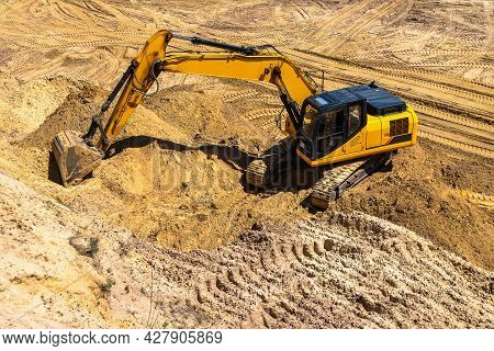 Closeup Of An Industrial Yellow Excavator Working In A Cave Quarry. Industry, Technology, Mining. He