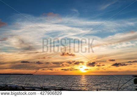 Reflection Of Sunlight In The Sea Waves. Sunset Over The Sea. Red And Yellow Sky In The Rays Of The