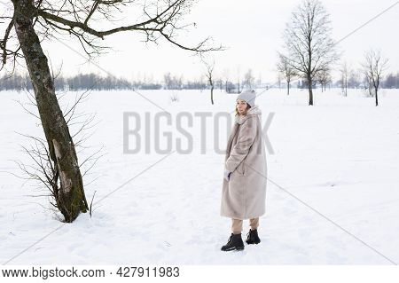 Young Girl In Beige Clothes, Fur Coat Made Of Artificial Fur Walks In Winter