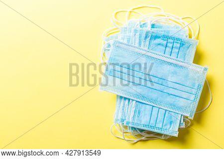 Close Up Of Virus Outbreak Inscription On Stack Of Medical Masks On Colored Background. Wuhan Virus.