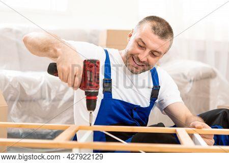 Happy Craftsman Working Using Drill Tool Fixing Wooden Cabinet Indoor