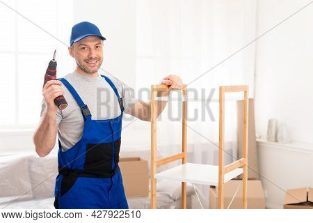Carpenter Posing With Electric Drill Standing Near Wooden Shelf Indoors