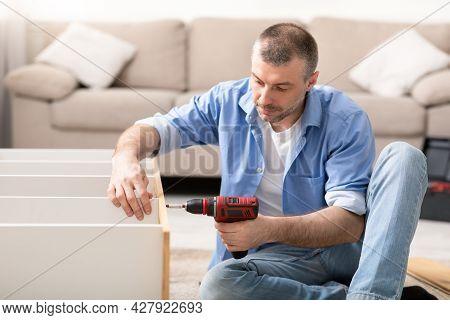Man Using Electric Drill Assembling Wooden Shelf Furnishing Room Indoors
