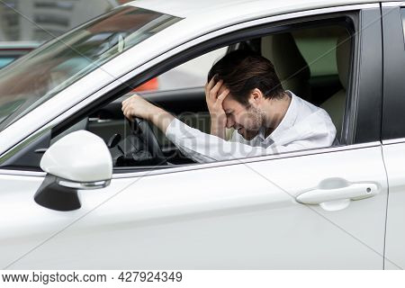 Businessman Sitting In Own Car Stuck In Traffic, Holding His Hand On Forehead And Nervously Waiting