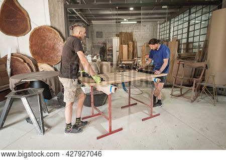 Two Carpenters Making Furniture In A Workshop. Woodworking And Crafts Tools