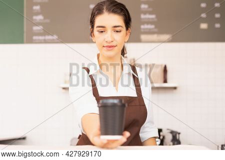 Beautiful Caucasian Barista Woman Shows Takeaway Coffee Cup In One Hand Forward And Looking To Coffe