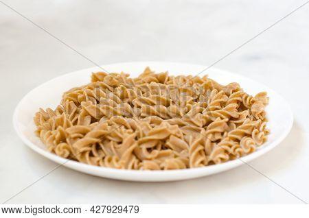 Organic Buckwheat Fusilli Pasta On A White Plate. Gluten Free Whole Grain Noodles. Healthy Food Conc