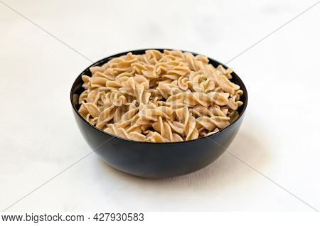 Organic Buckwheat Fusilli Pasta In A Black Bowl. Gluten Free Whole Grain Noodles. Healthy Food Conce