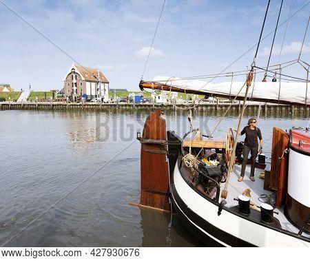 Oudeschild, Netherlands, 19 July 2021: Woman Steers Old Wooden Sailing Vessel In Port Of Oudeschild