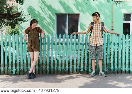 two teenagers boy and girl going down the street to school, they posing at the green fence near the house, education and back to school concept