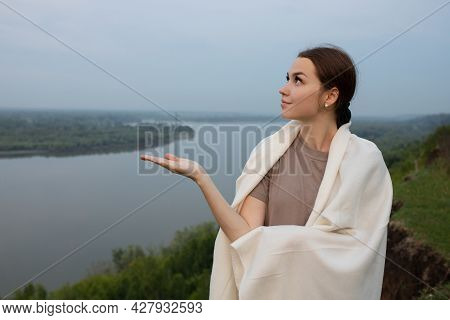 A Young Girl Stands On A Steep Cliff Wrapped In A White Blanket, In The Background The Ob River. The
