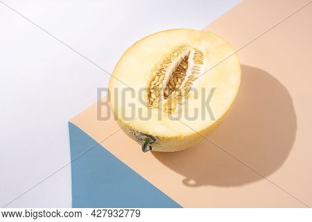 Half A Juicy Melon On A Yellow And Blue Background, Sunny, Beautiful Shadow, Modern Still Life.