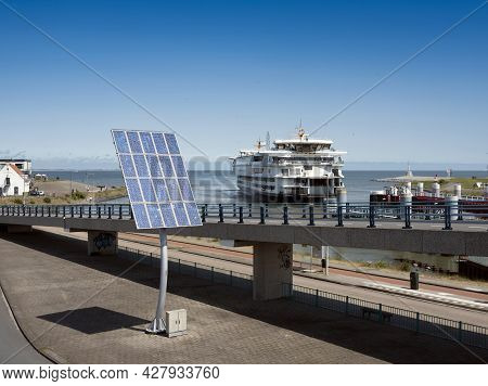 Solar Panels And Arriving Ferry From Texel At Port Of Den Helder In The Netherlands Under Blue Sky O