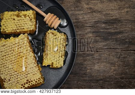 Closeup Honeycomb And Honey Dipper On Wooden Table